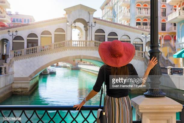 rear view of woman standing on bridge over canal - qatar stock pictures, royalty-free photos & images