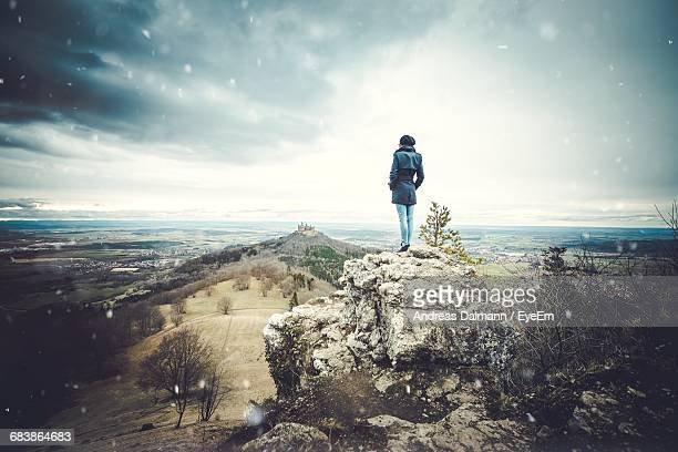 Rear View Of Woman Standing On Cliff Against Cloudy Sky During Snowfall