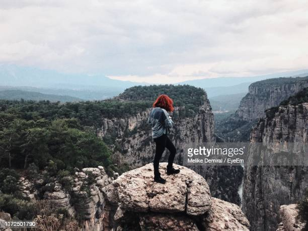 rear view of woman standing on cliff against cloudy sky - demiral stock pictures, royalty-free photos & images