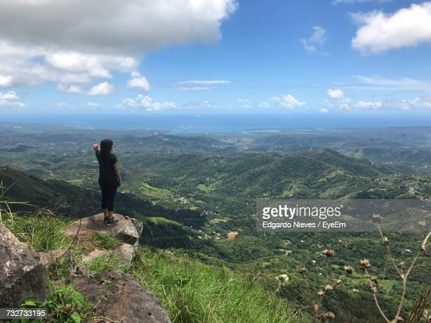 rear view of woman standing on cliff against landscape - paisajes de puerto rico fotografías e imágenes de stock
