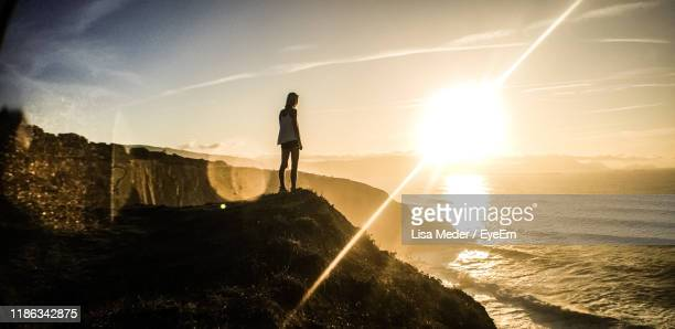 rear view of woman standing on cliff looking at sea - light natural phenomenon stock pictures, royalty-free photos & images