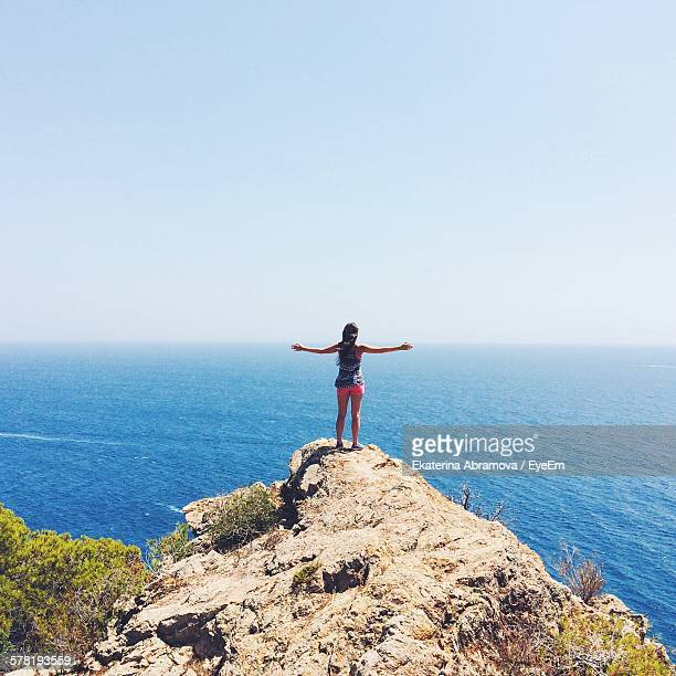 Rear View Of Woman Standing On Cliff While Looking At Sea Against Clear Sky