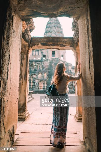 rear view of woman standing on doorway of ancient temple - kambodschanische kultur stock-fotos und bilder