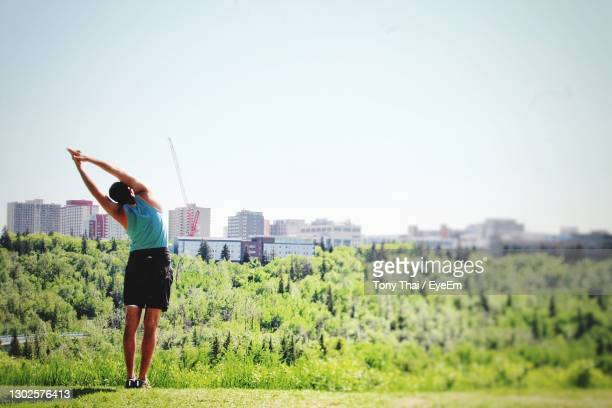 rear view of woman standing on field against clear sky - edmonton stock pictures, royalty-free photos & images