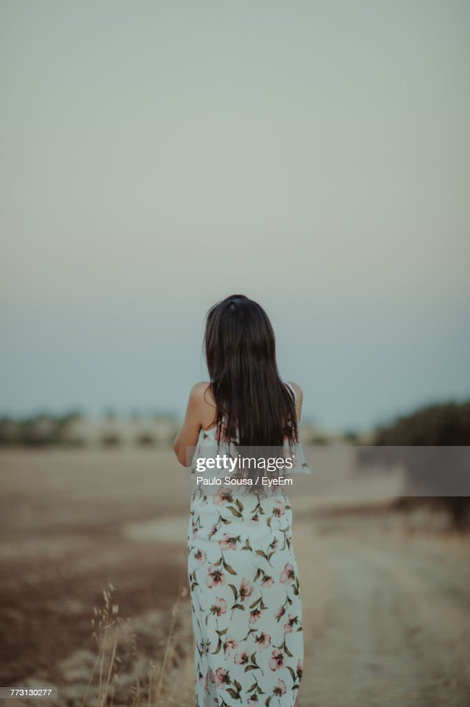 Rear View Of Woman Standing On Field Against Clear Sky : Stock Photo
