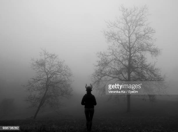 rear view of woman standing on field against sky during foggy weather - ksi stock photos and pictures