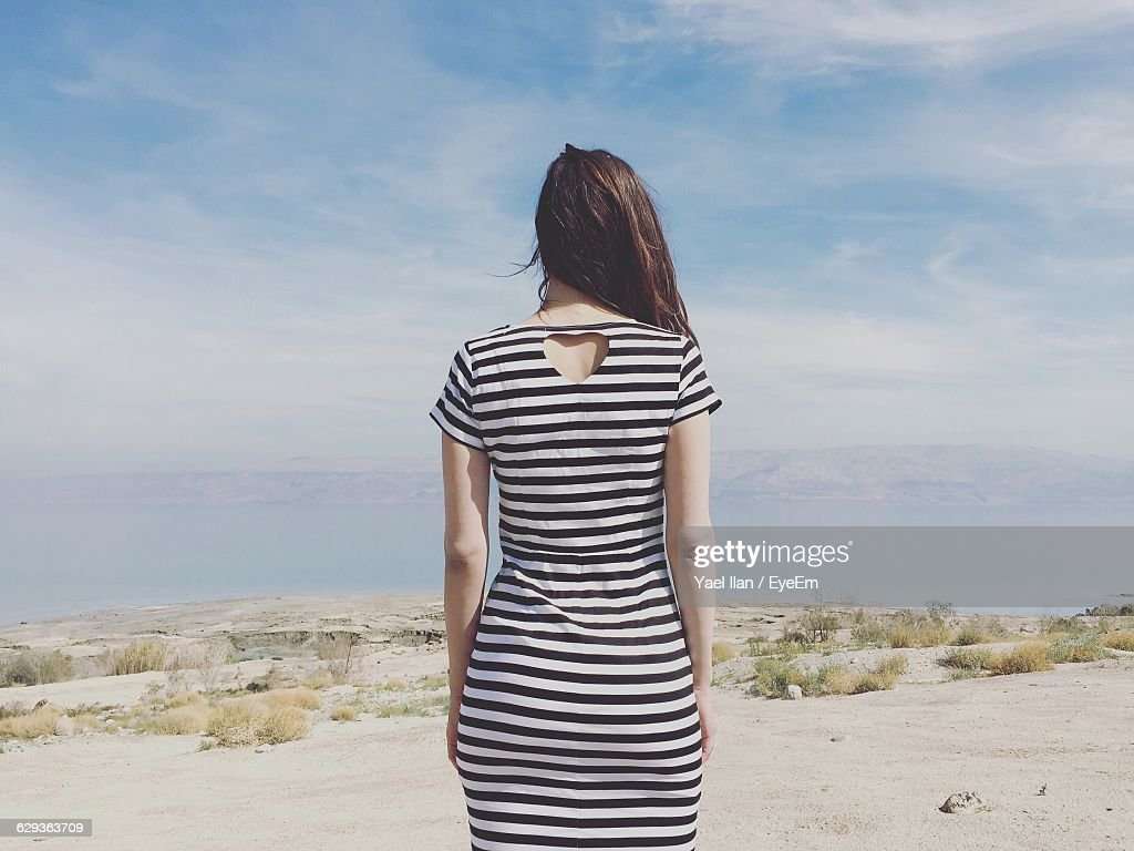 Rear View Of Woman Standing On Field Against Sky : Stock Photo