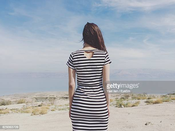 rear view of woman standing on field against sky - striped dress stock photos and pictures