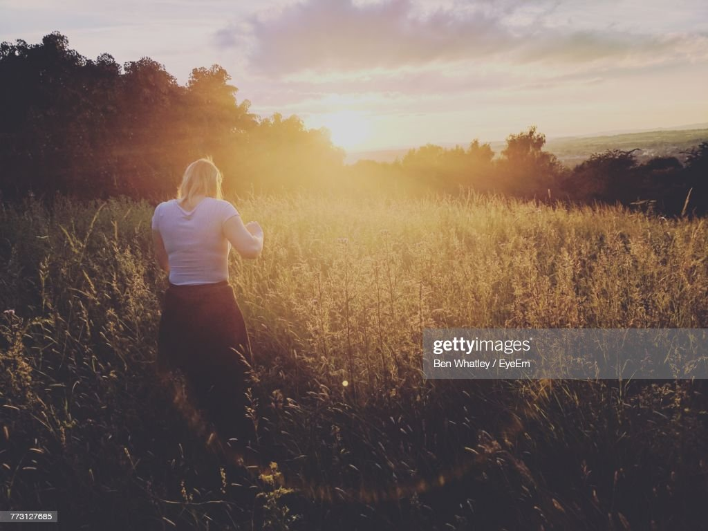 Rear View Of Woman Standing On Field Against Sky : Photo