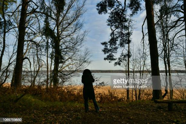 Rear View Of Woman Standing On Field Against Trees In Forest