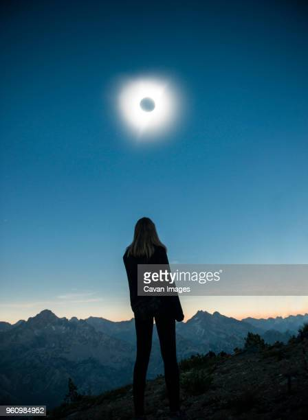 rear view of woman standing on field at sawtooth range during solar eclipse against sky - 天文 蝕 ストックフォトと画像