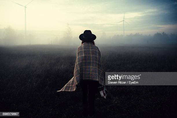 Rear View Of Woman Standing On Field In Foggy Weather