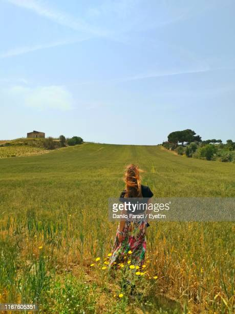 rear view of woman standing on field - southern europe stock pictures, royalty-free photos & images