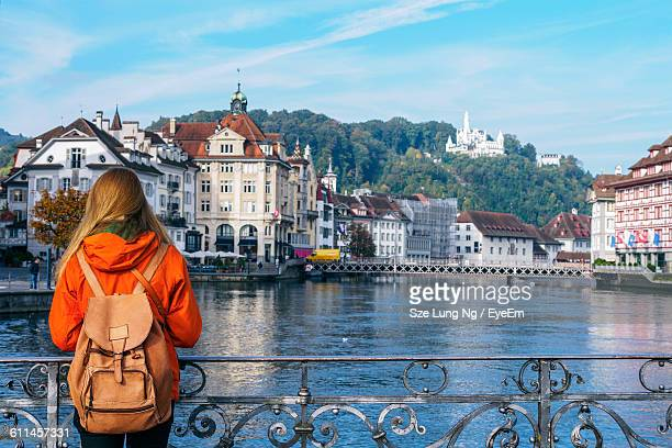 Rear View Of Woman Standing On Footbridge Over River