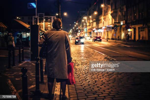 Rear View Of Woman Standing On Footpath By Road In City At Night