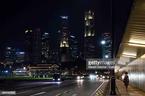Rear View Of Woman Standing On Footpath In City At Night