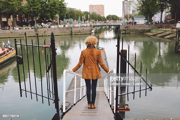 rear view of woman standing on footpath leading towards pier at river - bortes photos et images de collection