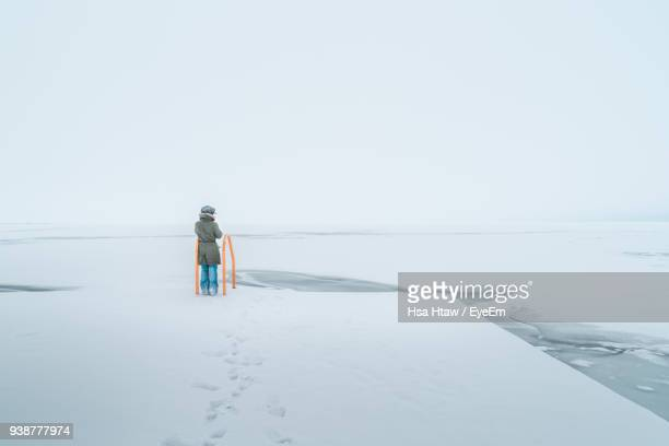 Rear View Of Woman Standing On Frozen Sea Against Clear Sky