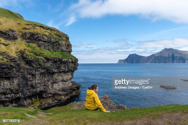 Rear View Of Woman Standing On Grass While Looking At Sea Against Sky
