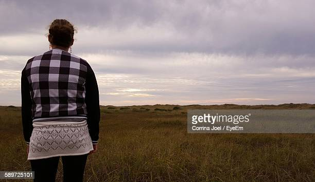 Rear View Of Woman Standing On Grassy Field Against Cloudy Sky