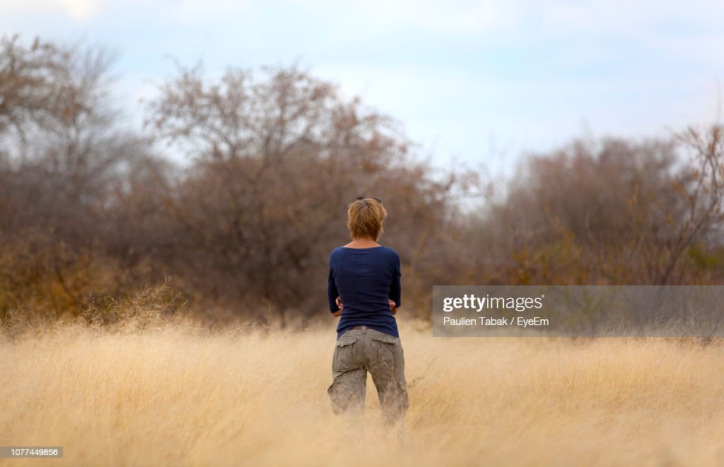Rear View Of Woman Standing On Grassy Field : Stockfoto