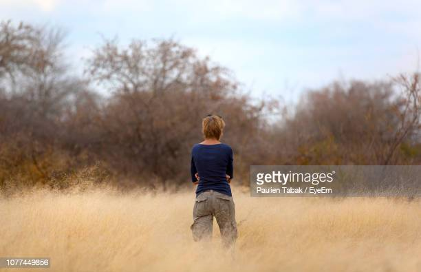 rear view of woman standing on grassy field - paulien tabak stock-fotos und bilder