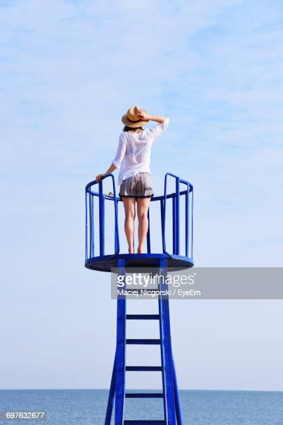 rear view of woman standing on lookout tower looking at sea against sky - lookout tower stock pictures, royalty-free photos & images