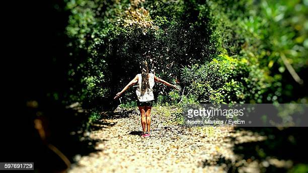 rear view of woman standing on messy field against trees - noemi foto e immagini stock
