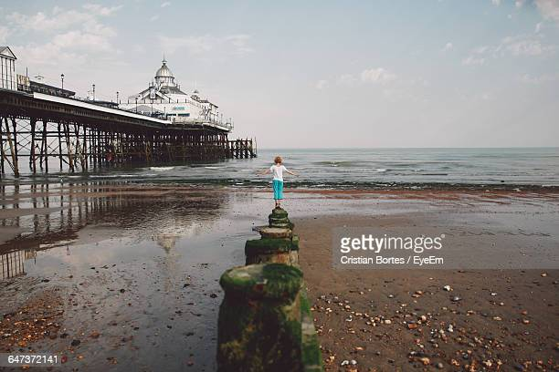 rear view of woman standing on moss covered wooden post at beach by eastbourne pier against sky - wide shot stock pictures, royalty-free photos & images
