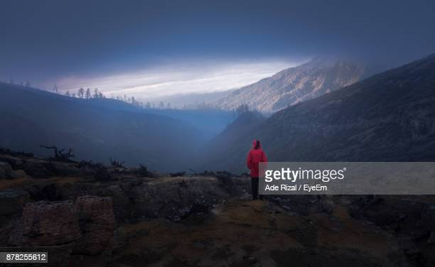rear view of woman standing on mountain against cloudy sky - ade rizal stock photos and pictures