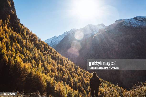 rear view of woman standing on mountain against sky during sunny day - fabrizio zampetti foto e immagini stock