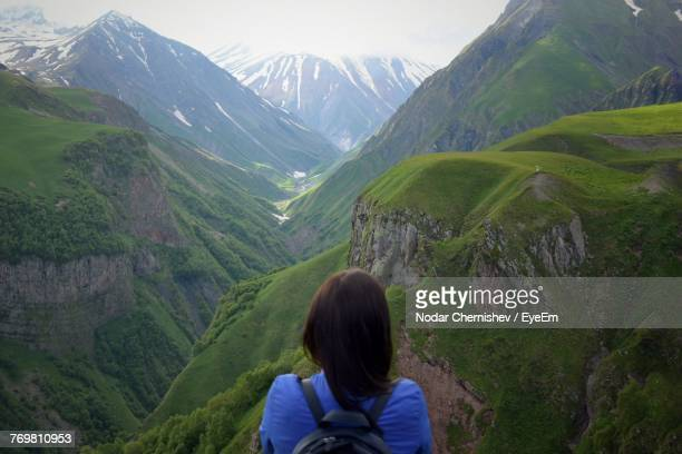 rear view of woman standing on mountain against sky - tbilisi stock pictures, royalty-free photos & images