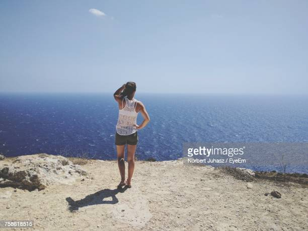 Rear View Of Woman Standing On Mountain By Sea Against Sky During Sunny Day