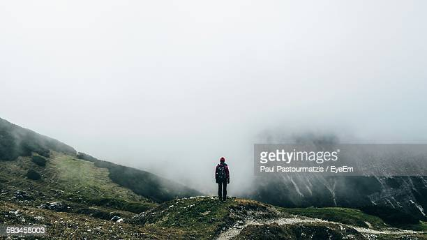 Rear View Of Woman Standing On Mountain During Foggy Weather