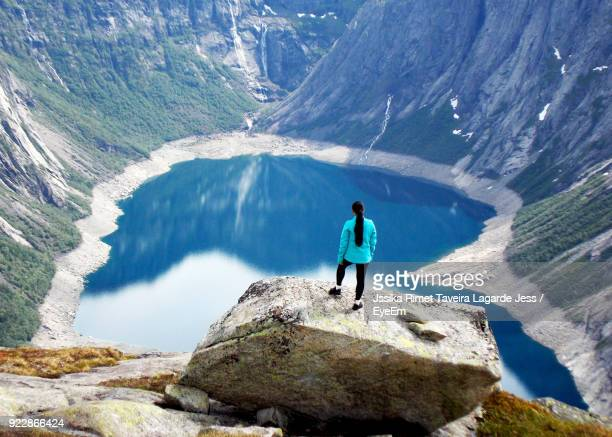 rear view of woman standing on mountain over lake - lagarde stock pictures, royalty-free photos & images