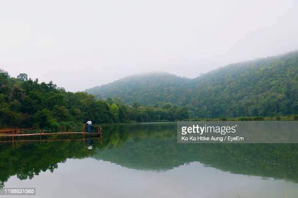 rear view of woman standing on pier over lake during foggy weather - ko ko htike aung stock pictures, royalty-free photos & images