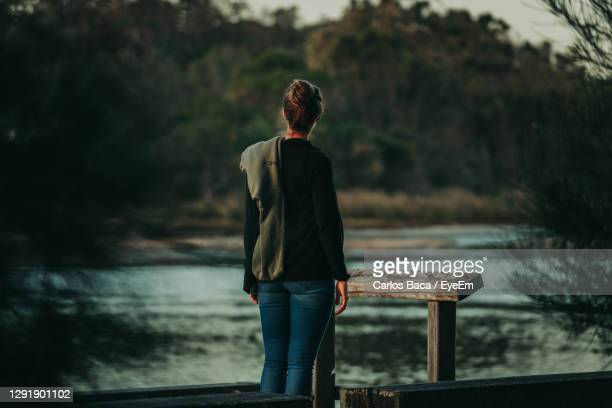 rear view of woman standing on pier over lake - batemans bay stock pictures, royalty-free photos & images