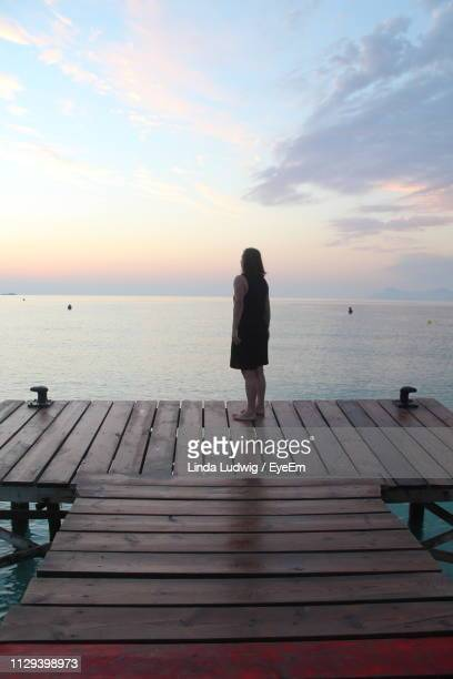 rear view of woman standing on pier over sea against cloudy sky during sunset - muro stock photos and pictures