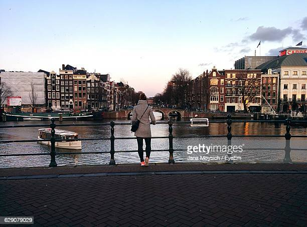 Rear View Of Woman Standing On Promenade By Canal In City Against Sky