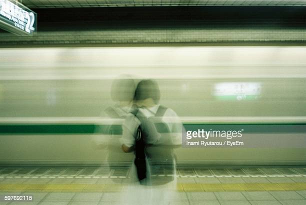 Rear View Of Woman Standing On Railroad Station Against Moving Train