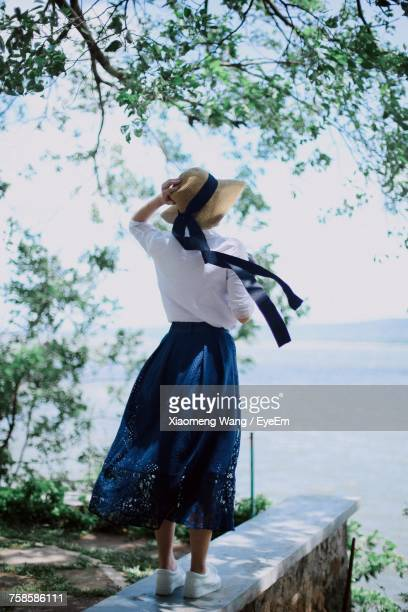 rear view of woman standing on retaining wall against sea - jupe vent photos et images de collection