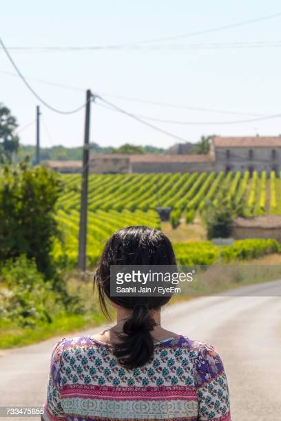 Rear View Of Woman Standing On Road Against Field During Sunny Day