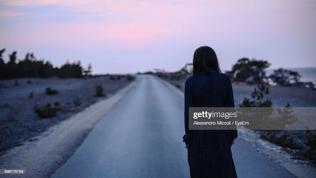Rear View Of Woman Standing On Road Against Sky During Sunset : Stock Photo