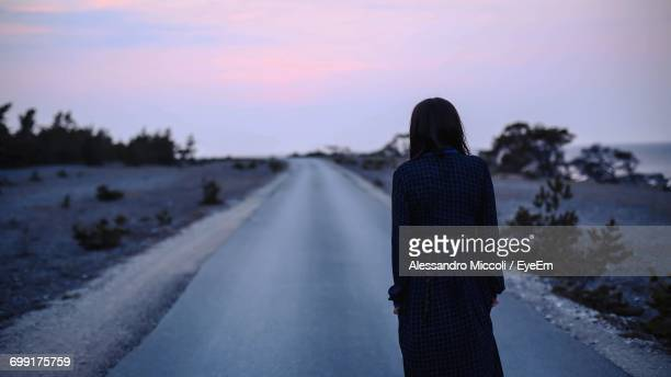 rear view of woman standing on road against sky during sunset - alessandro miccoli fotografías e imágenes de stock