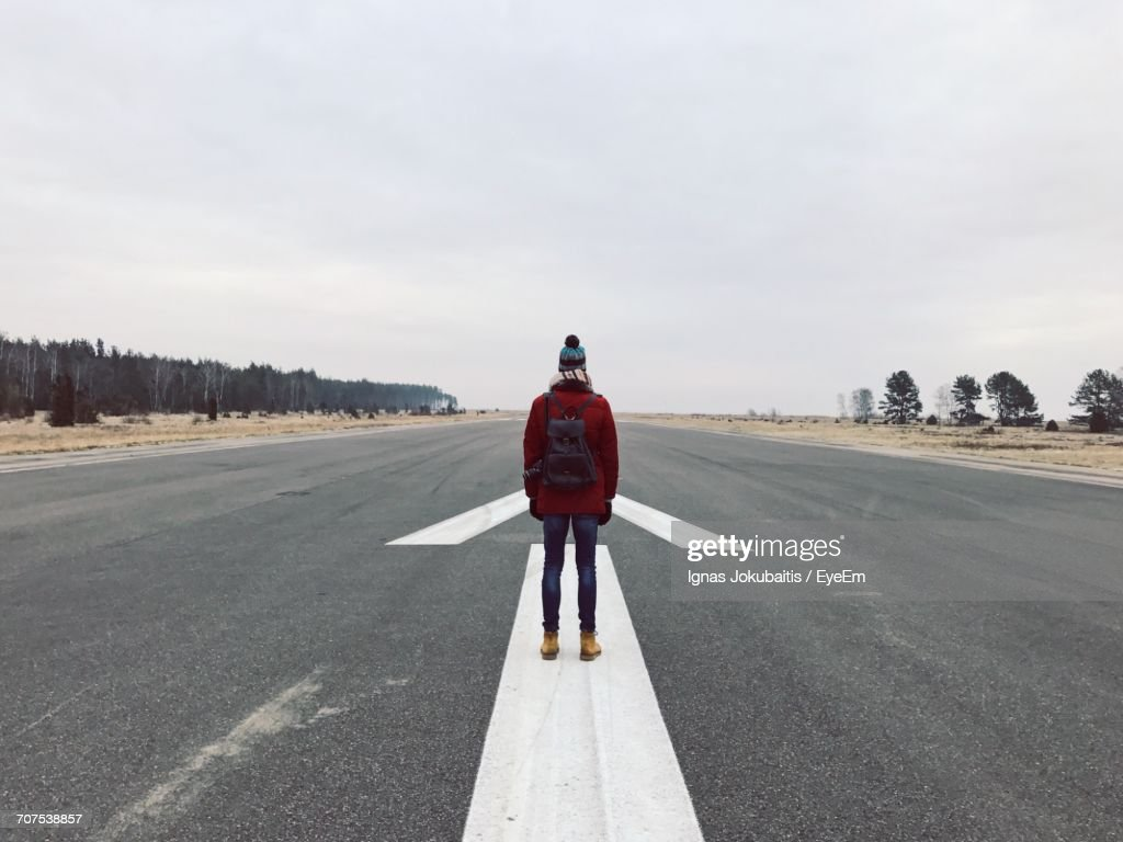 Rear View Of Woman Standing On Road Against Sky : Stock Photo