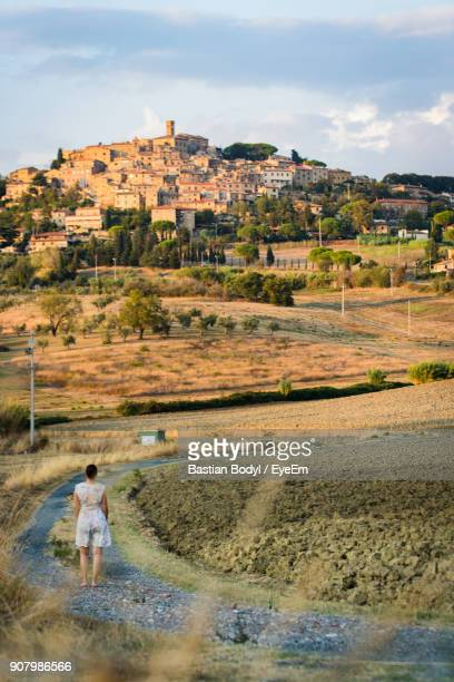 Rear View Of Woman Standing On Road Against Town On Hill Against Sky