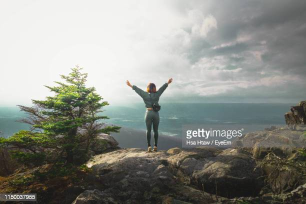rear view of woman standing on rock against sky - shenandoah_national_park stock pictures, royalty-free photos & images