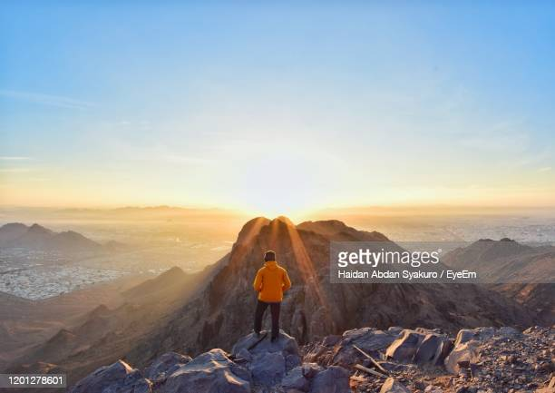 rear view of woman standing on rock against sky - riyadh stock pictures, royalty-free photos & images