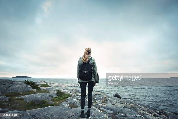 Rear view of woman standing on rock by sea against cloudy sky