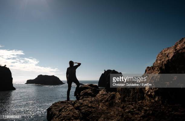 rear view of woman standing on rock by sea against sky - christian soldatke ストックフォトと画像